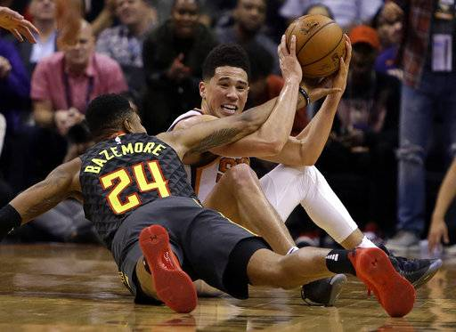 Phoenix Suns guard Devin Booker (1) and Atlanta Hawks guard Kent Bazemore vie for a loose ball in the second half during an NBA basketball game Tuesday, Jan. 2, 2018, in Phoenix. The Suns defeated the Hawks 104-103.