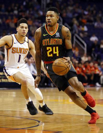 Atlanta Hawks guard Kent Bazemore (24) goes to the basket as Phoenix Suns guard Devin Booker defends in the first half during an NBA basketball game, Tuesday, Jan. 2, 2018, in Phoenix.
