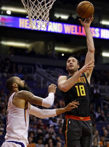 Atlanta Hawks center Miles Plumlee (18) shoots over Phoenix Suns center Tyson Chandler in the first half during an NBA basketball game, Tuesday, Jan. 2, 2018, in Phoenix.