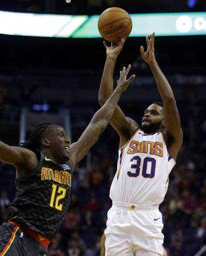 Phoenix Suns guard Troy Daniels (30) shoots over Atlanta Hawks forward Taurean Prince during the second half of an NBA basketball game Tuesday, Jan. 2, 2018, in Phoenix. The Suns defeated the Hawks 104-103.