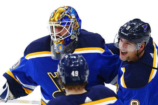 St. Louis Blues goaltender Carter Hutton is congratulated by Scottie Upshall, right, and Ivan Barbashev, of Russia, after the Blues defeated the New Jersey Devils in a shootout in an NHL hockey game Tuesday, Jan. 2, 2018, in St. Louis. The Blues won 3-2 in a shootout. (AP Photo/Billy Hurst)