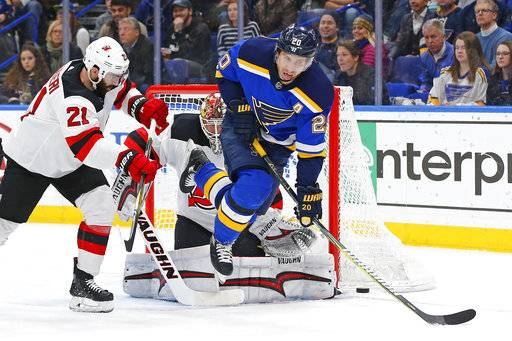 St. Louis Blues' Alexander Steen, right, attempts to deflect a shot in front of New Jersey Devils goaltender Keith Kinkaid, as Kyle Palmieri, left, defends during the second period of an NHL hockey game Tuesday, Jan. 2, 2018, in St. Louis.