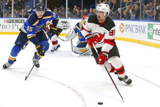 New Jersey Devils' Marcus Johansson, right, of Sweden, handles the puck as he is pressured by St. Louis Blues' Colton Parayko during the first period of an NHL hockey game Tuesday, Jan. 2, 2018, in St. Louis.