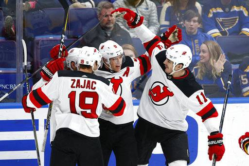 New Jersey Devils' Taylor Hall (9) is congratulated by teammates Travis Zajac (19) and Brian Boyle (11) after scoring a goal against the St. Louis Blues during the third period of an NHL hockey game Tuesday, Jan. 2, 2018, in St. Louis. The Blues won 3-2 in a shootout.
