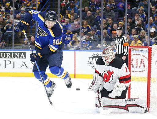 St. Louis Blues center Brayden Schenn hops clear of a teammate's shot against New Jersey Devils goaltender Keith Kinkaid during the first period of an NHL hockey game, Tuesday, Jan. 2, 2018, at the Scottrade Center in St. Louis. (Chris Lee/St. Louis Post-Dispatch via AP)
