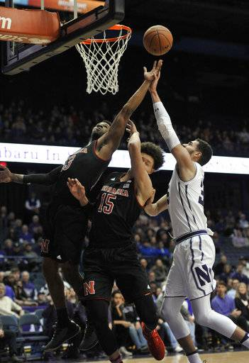 Northwestern's Aaron Falzon (35) and Nebraska's Anton Gill (13) and Isaiah Roby (15) reach for a rebound during the first half of an NCAA college basketball game Tuesday, Jan. 2, 2018, in Rosemont, Ill. (AP Photo/Paul Beaty)