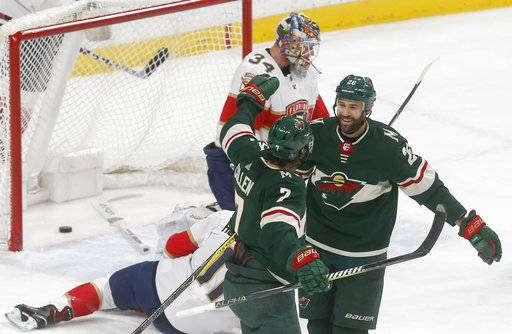 Minnesota Wild's Daniel Winnik, right, congratulates Matt Cullen on his his goal against Florida Panthers goalie James Reimer, top, during the first period of an NHL hockey game Tuesday, Jan. 2, 2018, in St. Paul, Minn.
