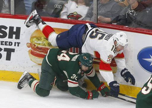 Florida Panthers' Aleksander Barkov, top, of Finland, topples over Minnesota Wild's Matt Dumba during the first period of an NHL hockey game Tuesday, Jan. 2, 2018, in St. Paul, Minn.