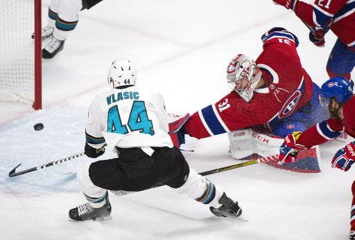 San Jose Sharks' Marc-Edouard Vlasic scores against Montreal Canadiens' Carey Price during the second period of an NHL hockey game in Montreal, Tuesday, Jan. 2, 2018. (Graham Hughes/The Canadian Press via AP)