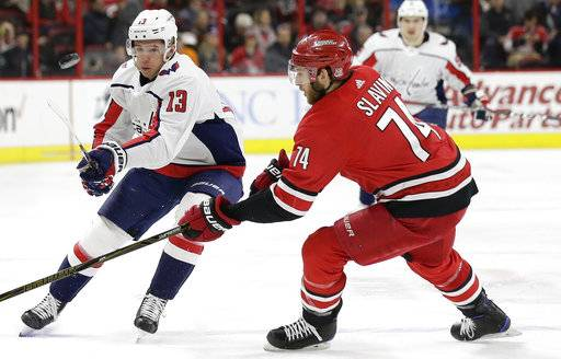 Carolina Hurricanes' Jaccob Slavin (74) defends as Washington Capitals' Jakub Vrana (13), of the Czech Republic, passes the puck during the first period of an NHL hockey game in Raleigh, N.C., Tuesday, Jan. 2, 2018. (AP Photo/Gerry Broome)