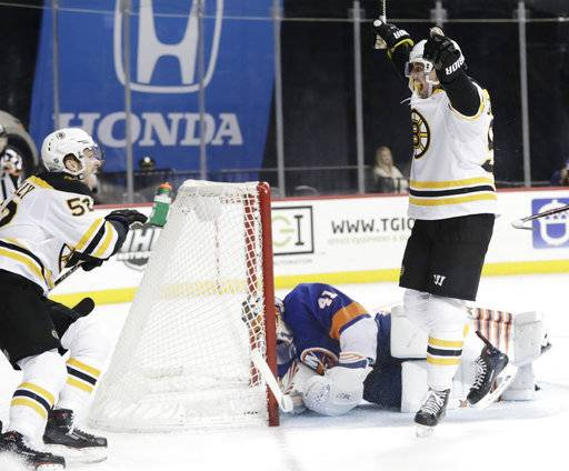 Boston Bruins' Tim Schaller, right, celebrates with teammate Sean Kuraly (52) after scoring a goal as New York Islanders goaltender Jaroslav Halak (41) gets up during the third period of an NHL hockey game Tuesday, Jan. 2, 2018, in New York. The Bruins won 5-1. (AP Photo/Frank Franklin II)