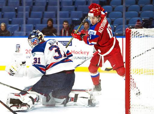 United States goaltender Joseph Woll (31) makes save as Russia forward Andrei Altybarmakyan (16) drives the net during the first period of a quarterfinal in the IIHF world junior hockey championships in Buffalo, N.Y., Tuesday, Jan. 2, 2018. (Nathan Denette/The Canadian Press via AP)