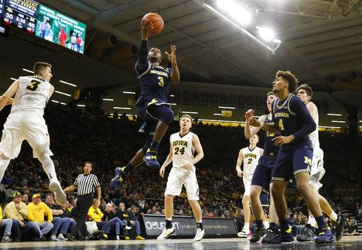 Michigan guard Zavier Simpson (3) drives to the basket past Iowa guard Jordan Bohannon, left, during the first half of an NCAA college basketball game Tuesday, Jan. 2, 2018, in Iowa City, Iowa. (AP Photo/Charlie Neibergall)
