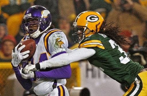 FILE - In this Jan. 9, 2005, file photo, Minnesota Vikings receiver Randy Moss catches a 34-yard touchdown pass in front of Green Bay Packers cornerback Al Harris during the fourth quarter of an NFC wild-card playoff football game in Green Bay, Wis. Star linebackers Ray Lewis and Brian Urlacher are among four first-time eligible former players selected in the 15 modern-era finalists for the Pro Football Hall of Fame's Class of 2018. Moss and guard Steve Hutchinson also made the cut to the finals as first-year eligibles.