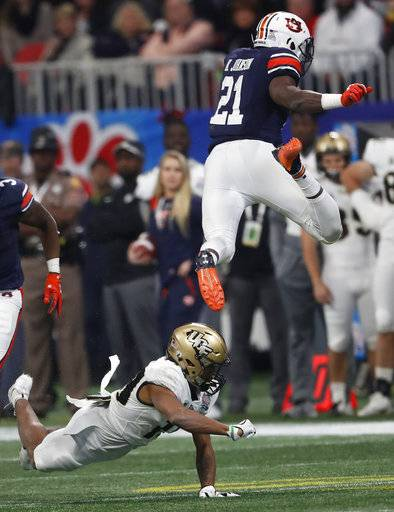 Auburn running back Kerryon Johnson (21) leaps over Central Florida defensive back Mike Hughes (19) during the first half of the Peach Bowl NCAA college football game, Monday, Jan. 1, 2018, in Atlanta. (AP Photo/John Bazemore)