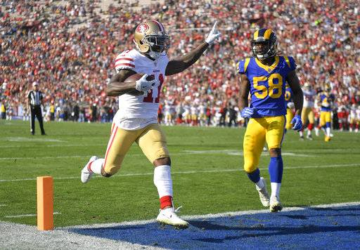 San Francisco 49ers wide receiver Marquise Goodwin, left, scores past Los Angeles Rams middle linebacker Cory Littleton during the first half of an NFL football game Sunday, Dec. 31, 2017, in Los Angeles.