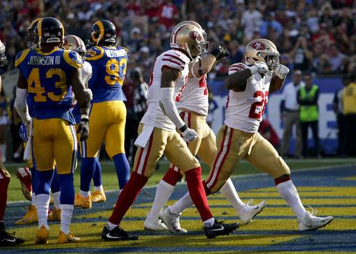 San Francisco 49ers running back Carlos Hyde, right, celebrates after scoring against the Los Angeles Rams during the first half of an NFL football game, Sunday, Dec. 31, 2017, in Los Angeles.