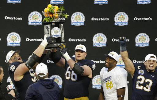 Notre Dame players, from left, Quenton Nelson, Mike McGlinchey, Miles Boykin and Drue Tranquill celebrate with the championship trophy after defeating LSU 21-17 in the Citrus Bowl NCAA college football game, Monday, Jan. 1, 2018, in Orlando, Fla.