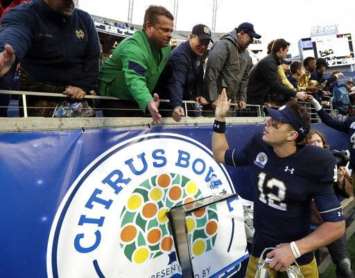 Notre Dame quarterback Ian Book (12) high fives fans after defeating LSU 21-17 in the Citrus Bowl NCAA college football game, Monday, Jan. 1, 2018, in Orlando, Fla.