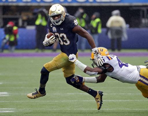 Notre Dame running back Josh Adams (33) makes a move to escape a tackle by LSU linebacker Michael Divinity Jr. during the second half of the Citrus Bowl NCAA college football game, Monday, Jan. 1, 2018, in Orlando, Fla. Notre Dame won 21-17.