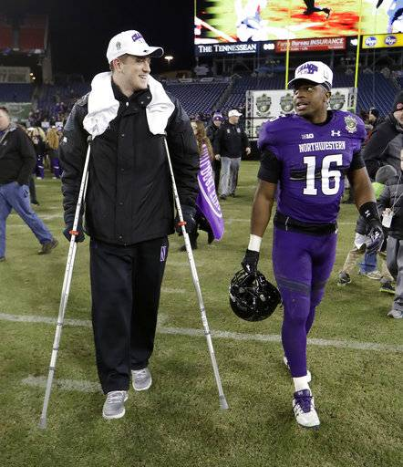 Northwestern quarterback Clayton Thorson, left, walks with safety Godwin Igwebuike (16) after Northwestern beat Kentucky 24-23 in the Music City Bowl NCAA college football game Friday, Dec. 29, 2017, in Nashville, Tenn. Thorson was injured during the game.