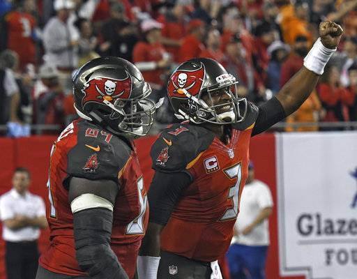 Tampa Bay Buccaneers quarterback Jameis Winston (3) celebrates with offensive guard Kevin Pamphile (64) after the Buccaneers scored against the New Orleans Saints during the second half of an NFL football game Sunday, Dec. 31, 2017, in Tampa, Fla. The Buccaneers won the game 31-24. (AP Photo/Jason Behnken)