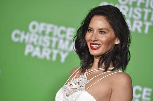 "FILE - In this Dec. 7, 2016, file photo, Olivia Munn arrives at the premiere of ""Office Christmas Party"" at the Village Theatre Westwood in Los Angeles. Organizers said Wednesday, Jan. 3 2018, that Munn will host the 2018 Critics' Choice awards to be broadcast Jan. 11 on the CW. (Photo by Jordan Strauss/Invision/AP, File)"