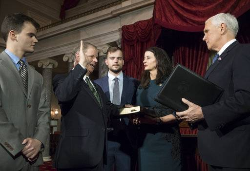 Vice President Mike Pence, right, administers the Senate oath of office during a mock swearing in ceremony in the Old Senate Chamber to Sen. Doug Jones, D-Ala., second from left, with his wife Louise Jones, second from right, Wednesday, Jan. 3, 2018 on Capitol Hill in Washington.  They are joined at far left by their son Christopher Jones, and son Carson Jones, center.  Jones defeated Republican Roy Moore in a special election to take the seat once held by Attorney General Jeff Sessions.
