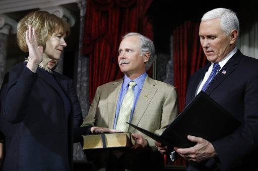 Vice President Mike Pence, right, administers the Senate oath of office during a mock swearing in ceremony in the Old Senate Chamber to Sen. Tina Smith, D-Minn., left, with her husband Archie Smith, center, Wednesday, Jan. 3, 2018 on Capitol Hill in Washington.  Sen. Smith will take over from Al Franken who resigned.