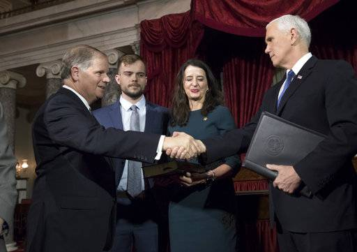 Vice President Mike Pence, right, shakes hands with Sen. Doug Jones, D-Ala., left, after administering the Senate oath of office during a mock swearing in ceremony in the Old Senate Chamber to Jones, with his wife Louise Jones, second from right, Wednesday, Jan. 3, 2018 on Capitol Hill in Washington.  They are joined by their son, Carson Jones, center.  Jones defeated Republican Roy Moore in a special election to take the seat once held by Attorney General Jeff Sessions.