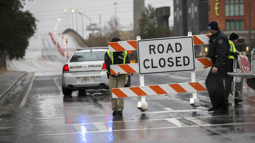 Two Savannah Chatham Metro Police officers set up a barricade in front of a bridge that was closed due to ice on the road, Wednesday, Jan. 3, 2018, in Savannah, Ga. A brutal winter storm scattered a wintry mix of snow, sleet and freezing rain from normally balmy Florida up the Southeast seaboard Wednesday.