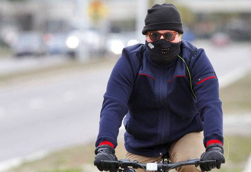 A man rides his bicycle along U.S. 90 in Biloxi, Miss., on Wednesday, Jan. 3, 2018. Warming shelters were opened across the South as freeze watches and warnings blanketed the region, including hard freeze warnings for much of Louisiana, Mississippi and Alabama. (John Fitzhugh/The Sun Herald via AP)