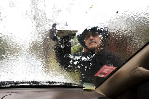 Omar Elkhalidi uses a wood shim to scrape ice off his windshield that accumulated overnight from freezing temperatures, Wednesday, Jan. 3, 2018, in Savannah, Ga. Only a few motorists ventured out in freezing rain that coated bridges and ramps with ice, forcing police to close roads and highways in Savannah.