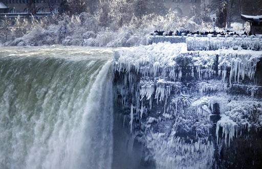 Visitors take photographs at the brink of the Horseshoe Falls in Niagara Falls, Ont., Tuesday, Jan. 2, 2018.  Almost every year frigid temperatures transform the falls into an icy winter wonderland when the mist is blown back, freezing on the landscape.  (Aaron Lynett/The Canadian Press via AP)