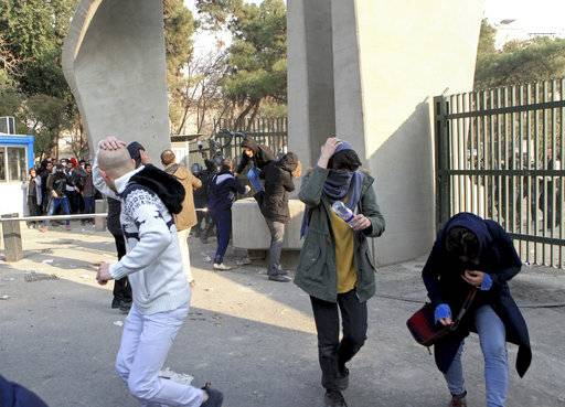 In this photo taken on Saturday, Dec. 30, 2017, by an individual not employed by the Associated Press and obtained by the AP outside Iran, university students run away from stones thrown by police during an anti-government protest inside Tehran University, in Tehran, Iran. Demonstrations, the largest seen in Iran since its disputed 2009 presidential election, have brought six days of unrest across the country and resulted in over 20 deaths.