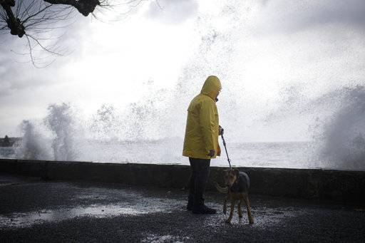 A stroller walks with a dog as winter storm Burglind blows over the Lake Constance, Wednesday, Jan. 3, 2018, in Rorschach, Switzerland. The storm is expected to cause strong gusts of wind of up to 150 kilometers per hour in some mountain areas. (Gian Ehrenzeller/Keystone via AP)