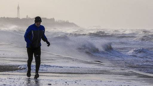 A man jogs along the beach in Blackpool northwest England as a storm lashed Britain with violent storm-force winds of up to 100mph, leaving thousands of homes without power and hitting transport links Wednesday Jan. 3, 2018. (Peter Byrne/PA via AP)