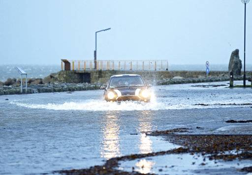 A car drives through a flooded car park in Salthill, Galway, Ireland Wednesday Jan. 3, 2018 as Storm Eleanor lashed Britain and Ireland with violent storm-force winds of up to 100mph, leaving thousands of homes without power and hitting transport links. (Brian Lawless/PA via AP)