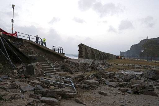 A partially collapsed harbour wall in Portreath, Cornwall, Wednesday Jan. 3, 2018 after Storm Eleanor lashed Britain and Ireland with violent storm-force winds of up to 100mph, leaving thousands of homes without power and hitting transport links.(Steve Parsons/PA via AP)