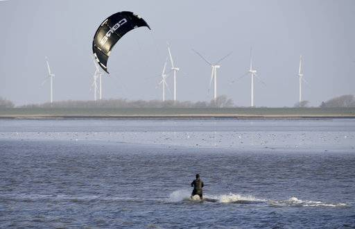 A kitesurfer makes use of the wind in Dagebuell, Germany, Wednesday, Jan. 3, 2018. A storm with hurricane-like winds is expected for the afternoon. (Carsten Rehder/dpa via AP)