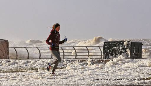 A woman jogs through sea foam in Blackpool northwest England as a storm lashed Britain with violent storm-force winds of up to 100mph, leaving thousands of homes without power and hitting transport links Wednesday Jan. 3, 2018. (Peter Byrne/PA via AP)