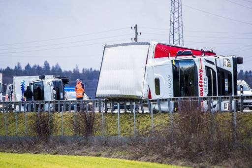 Two trucks lie on their sides and block the highway A1 between Oensingen and Niederbipp, Switzerland, Wednesday, Jan. 3, 2018, during heavy winds. The winter storm Burglind has caused damage and traffic disturbances all over Switzerland. (Christian Merz/Keystone via AP)