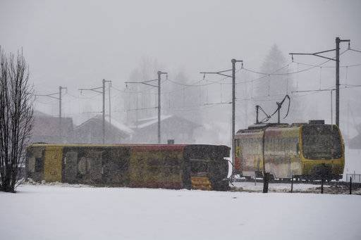 A derailed coach of a train lies in a field in Boden near Lenk, in the Canton of Bern, Switzerland, Wednesday, Jan. 3, 2018. Several people have been injured, when the train derailed due to the heavy winds of the storm Burglind. (Anthony Anex/Keystone via AP)