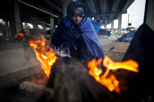 Tony Sampson, who received a blanket from Star of Hope's Love in Action van, tries to warm up by a fire under the Eastex Freeway as temperatures hover in the 30s Tuesday, Jan. 2, 2018, in Houston. Plunging overnight temperatures in Texas brought rare snow flurries as far south as Austin, and accidents racked up on icy roads across the state. (Michael Ciaglo/Houston Chronicle via AP)