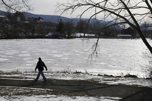 A man walks past a frozen part of the Hudson River in Beacon, N.Y., Wednesday, Jan. 3, 2018. Bitterly cold temperatures gripped much of the nation on Tuesday, testing the mettle of even winter-wise northerners and delivering a shock to those accustomed to far milder weather in the South.