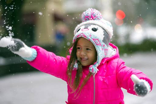 Sydney Freed, 4, of Orlando, Fla., throws one of her first snowballs at her father, Wednesday, Jan. 3, 2018, in Savannah, Ga.