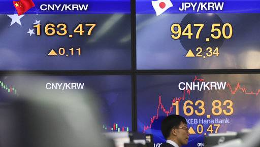 A currency trader walks by the screens showing the foreign exchange rates at the foreign exchange dealing room in Seoul, South Korea, Wednesday, Jan. 3, 2018. Strong manufacturing data and overnight gains on Wall Street gave Asian markets a boost on Wednesday.