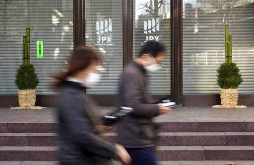 A man and a woman walk past Tokyo Stock Exchange which is closes for New Year's holidays in Tokyo Wednesday, Jan. 3, 2018. Strong manufacturing data and overnight gains on Wall Street gave Asian markets a boost on Wednesday. Markets in Japan were closed for New Year holidays.