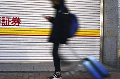 A man with a suite case walks past a securities firm which is closed for New Year's holidays in Tokyo Wednesday, Jan. 3, 2018. Strong manufacturing data and overnight gains on Wall Street gave Asian markets a boost on Wednesday. Markets in Japan were closed for New Year holidays.