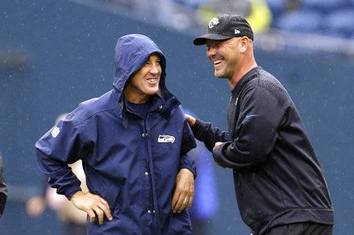 FILE - In this Sept. 22, 2013, file photo, Seattle Seahawks head coach Pete Carroll, left, and Jacksonville Jaguars head coach Gus Bradley talk in the rain before an NFL football game in Seattle. The scheme that carried the Seahawks to consecutive Super Bowls (2013-14) has become increasingly popular around the league. It helped Atlanta get to the big game last year and was the catalyst for Jacksonville's stunning turnaround this season.